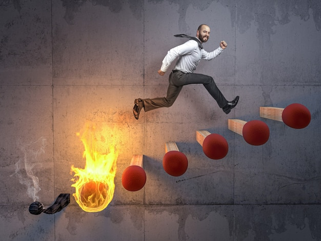 Бизнесмен прыгает по лестнице из спичек, которые вот-вот загорятся. Premium Фотографии