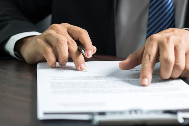 Businessman or lawyer reading and signing on contract paper Premium Photo