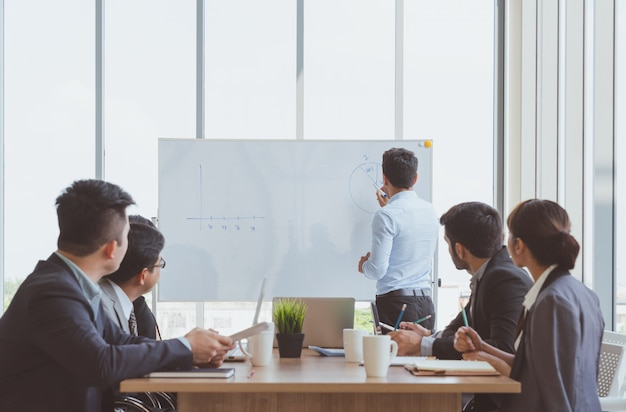 Businessman leader writing on the whiteboard present business marketing graph while meeting with colleagues in office.business team meeting presentation,conference planning business concept Premium Photo
