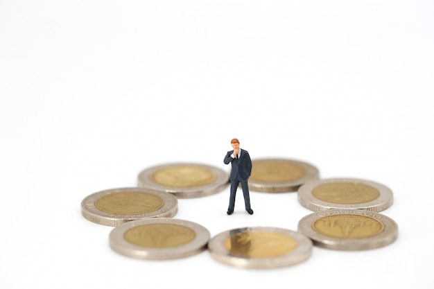 Businessman looking around coins and thinking something Premium Photo