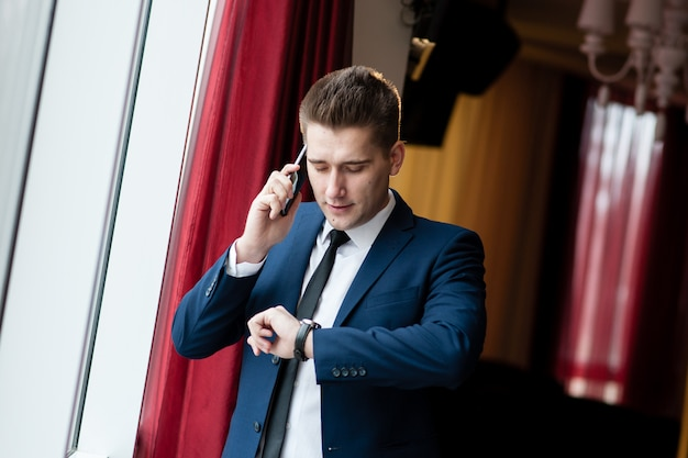 Businessman looking at clock and talking on the phone Premium Photo