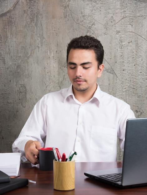 Бизнесмен, глядя на чашку чая за офисным столом. Бесплатные Фотографии