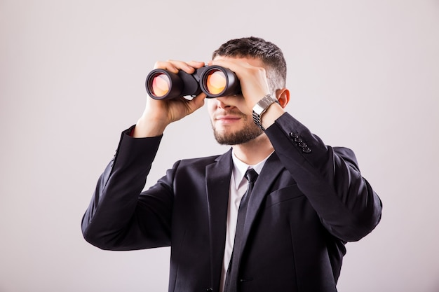 Businessman looking through binoculars isolated on white wall Free Photo