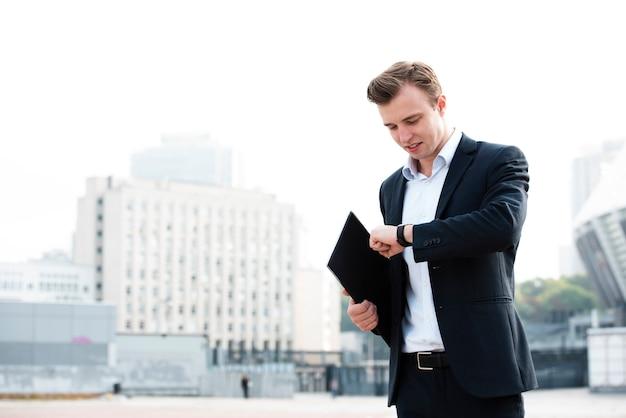 Businessman looking at wrist watch Free Photo