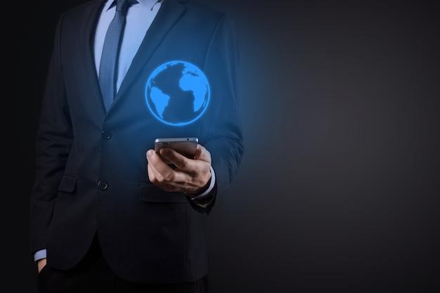 地球のアイコン、デジタルグローブを持っているビジネスマンの男の手。 Premium写真