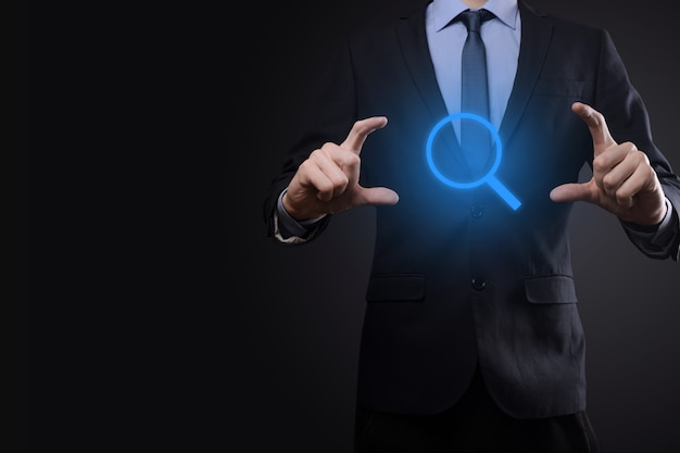 Businessman, man hold in hand magnifying glass icon.business, technology and internet concept Premium Photo