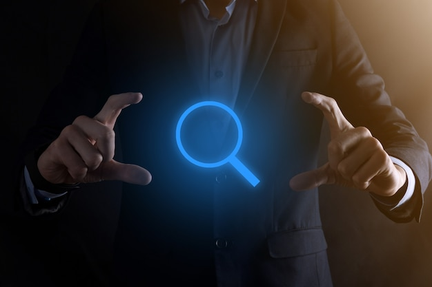 Businessman, man hold in hand magnifying glass icon Premium Photo
