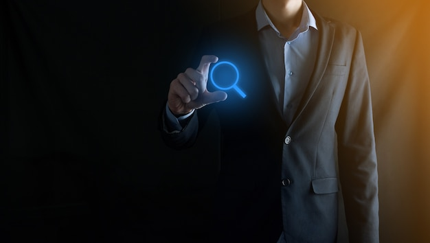 Businessman man hold in hand magnifying glass iconbusiness technology and internet concept Premium Photo