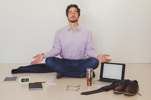 Businessman meditating on floor Free Photo