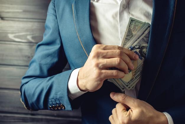 Предприниматель, член или сотрудник кладет взятку в карман Premium Фотографии