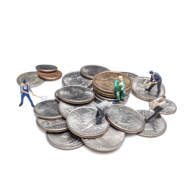 Businessman miniature figure after retirement concept idea with coin focus on old man. Premium Photo