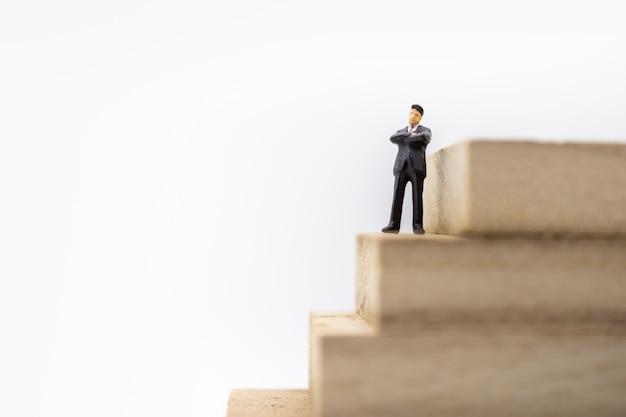 Businessman miniature figure standing on stack of wooden block  stair stack of wooden block Premium Photo