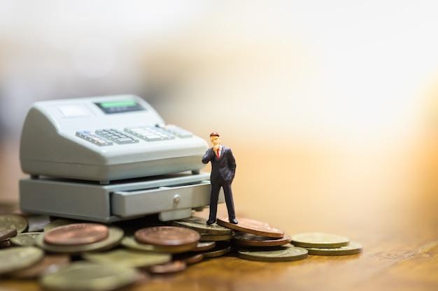 Businessman miniature standing on coins and cashier machine toy. Premium Photo