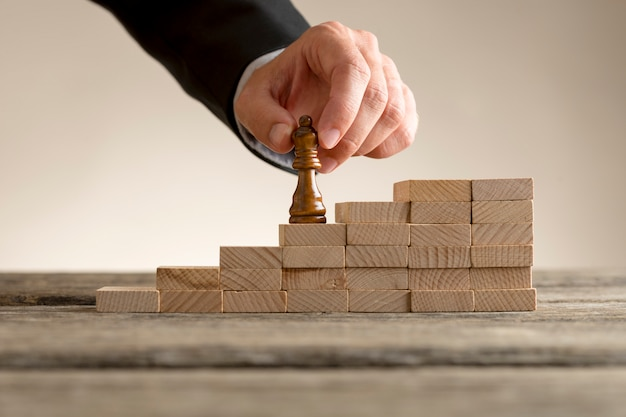 Businessman moving the queen piece up a series of steps Premium Photo