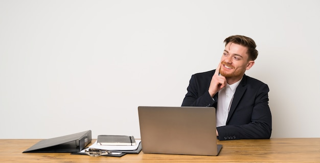 Businessman in a office thinking an idea while looking up Premium Photo