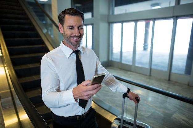 Бизнесмен на эскалаторе с помощью мобильного телефона Бесплатные Фотографии