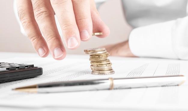 Бизнесмен или бухгалтер, считая деньги и делая стопку монет Premium Фотографии