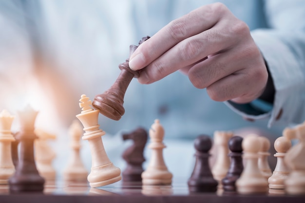 Businessman play with chess game in competition success play, concept strategy and successful management or leadership Premium Photo