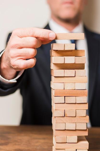 Businessman playing jenga Free Photo