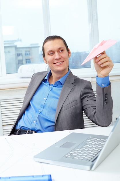 Businessman playing with a paper plane Free Photo