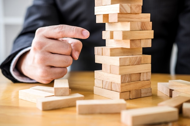 Businessman playing the wood game, hands of executive placing block Premium Photo