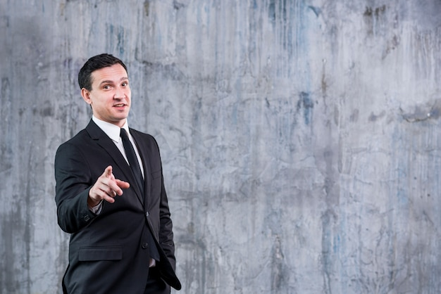 Businessman pointing at camera against grey wall Free Photo