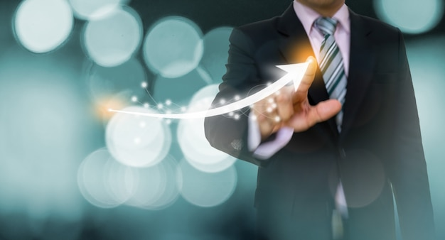 Businessman pointing graph and arrow concept Premium Photo