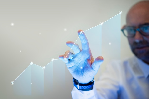 Businessman pointing his finger to a growth graph Free Photo