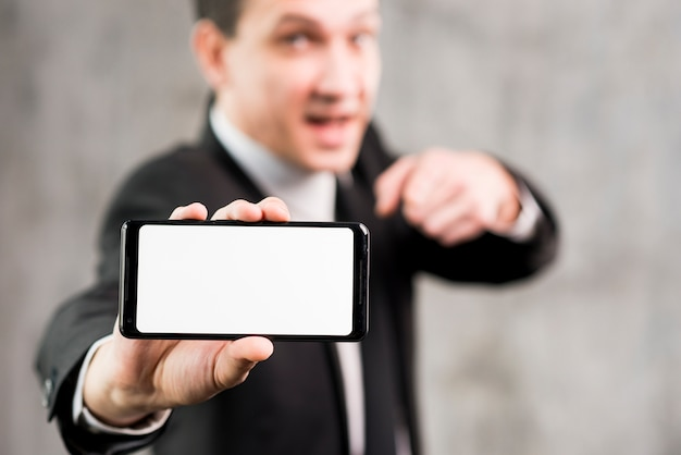 Businessman pointing at smartphone with blank display Free Photo