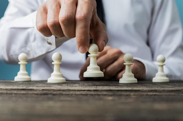 他の前に白いポーンチェスの駒を配置するビジネスマン Premium写真