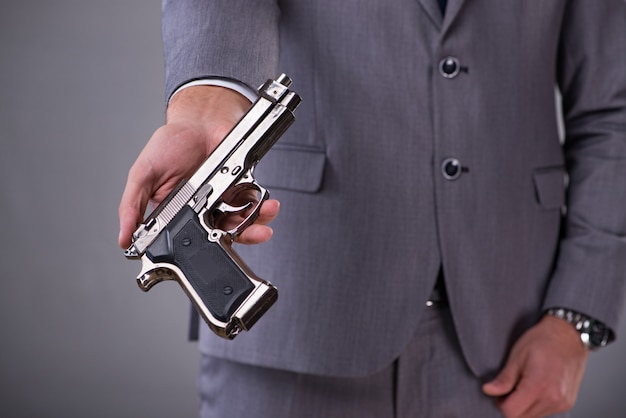 Businessman pulling the gun out of pocket Premium Photo