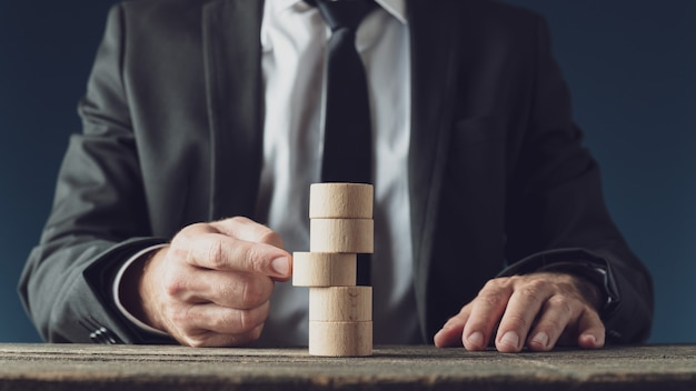 Businessman pushing a wooden cut circle in a stack of them in conceptual image of business vision and strategy. Premium Photo