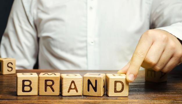 Бизнесмен ставит деревянные блоки со словом бренда. бизнес, маркетинг и реклама. Premium Фотографии