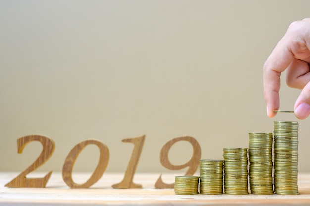 """Businessman putting and accounting money with """"2019"""" number Premium Photo"""