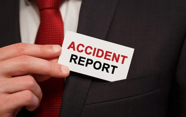Businessman putting a card with text accident report in the pocket Premium Photo