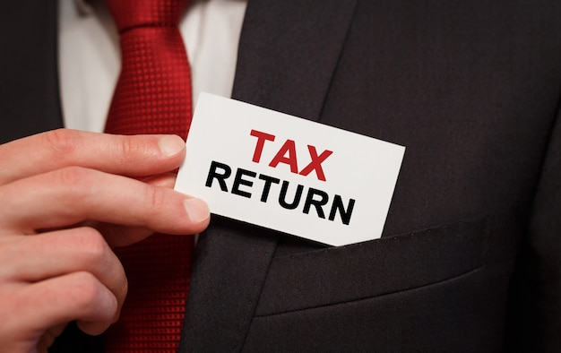 Premium Photo - Businessman putting a card with text tax return in the pocket