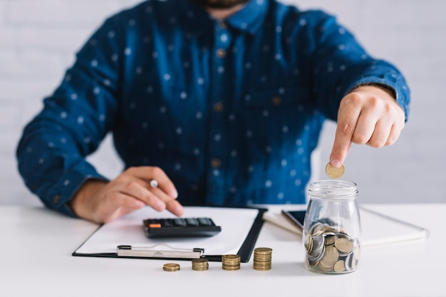Businessman putting coins in jar using calculator at workplace Free Photo