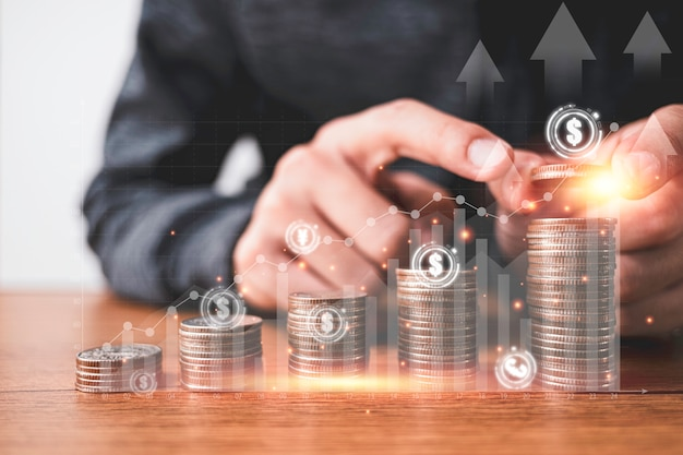 Businessman putting coins stacking with virtual graph and currency sign such as dollar pound sterling yen yuan and euro. business investment and saving profit concept. Premium Photo