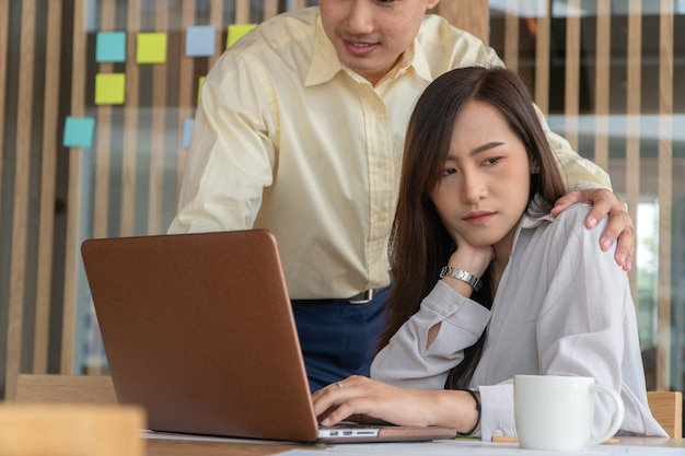 職場のオフィスで女性従業員の肩に手を置くビジネスマン。 Premium写真