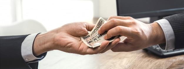 Businessman putting money in his partner hand Premium Photo