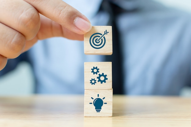 Businessman putting wooden block on top with icons Premium Photo