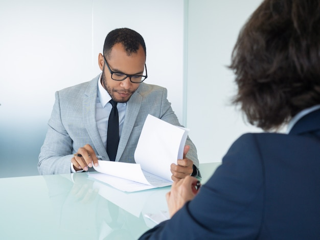 Businessman reading contract during meeting Free Photo