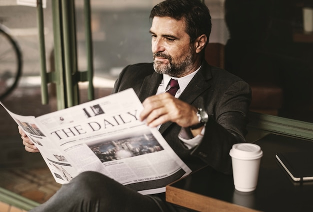 Businessman reading the daily news Free Photo