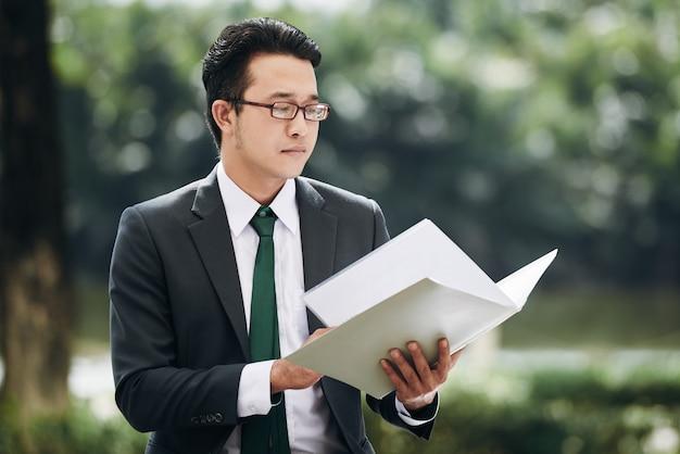 Businessman reading document Free Photo