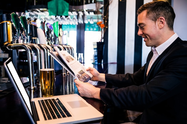 Businessman reading the news and using laptop at the counter in a bar Premium Photo