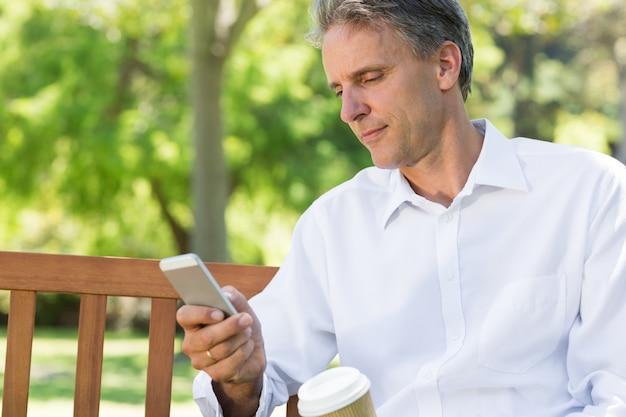 Businessman reading text message on mobile phone Premium Photo