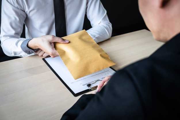 Businessman receive bribe money in envelope to business people to give success the deal contract Premium Photo