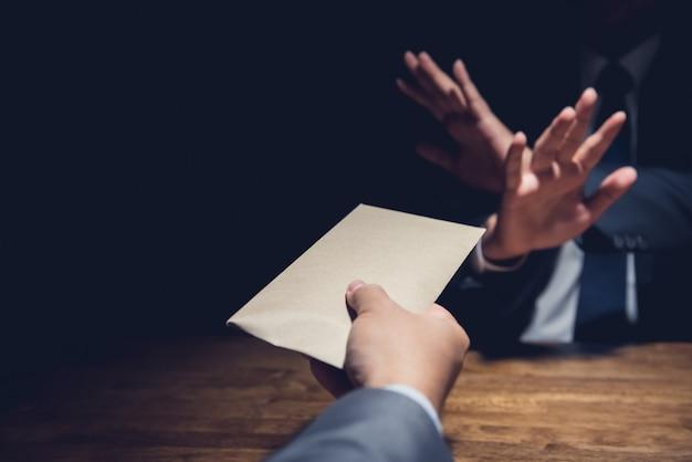 Businessman rejecting money in the envelope, anti bribery concept Premium Photo