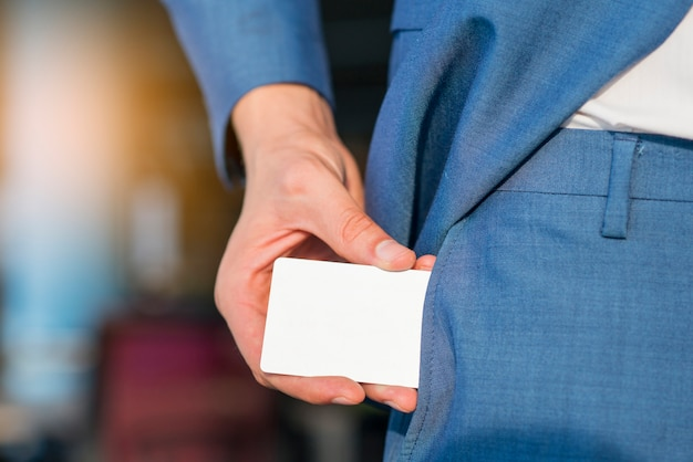 Businessman removing blank white card from his pocket Free Photo
