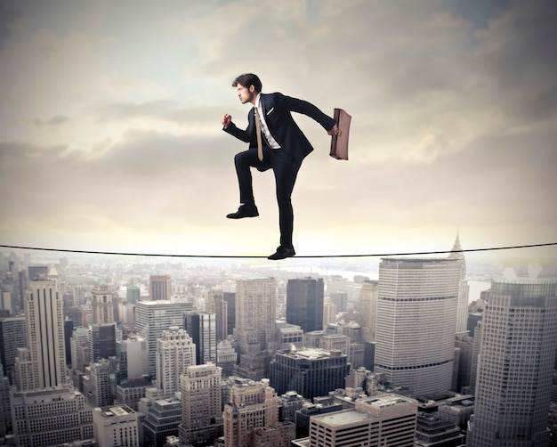Businessman risking and balancing Premium Photo